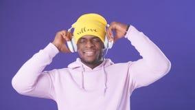 Ευτυχής σκοτεινός-ξεφλουδισμένος τύπος στο hoodie και το κίτρινο καπέλο που ακούνε τις αγαπημένες διαδρομές στα ακουστικά φιλμ μικρού μήκους