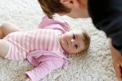 Ευτυχής υπερήφανος νέος πατέρας που έχει τη διασκέδαση με τη νεογέννητη κόρη μωρών, οικογενειακό πορτρέτο από κοινού Μπαμπάς με τ στοκ εικόνα