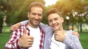 Ευτυχείς γιος και πατέρας που παρουσιάζουν αντίχειρας-επάνω, που απολαμβάνουν το χόμπι μαζί, πικ-νίκ στοκ φωτογραφίες