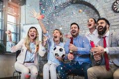 Ευτυχείς επιχειρηματίες ή οπαδοί ποδοσφαίρου που προσέχουν το ποδόσφαιρο στη TV και που γιορτάζουν τη νίκη στοκ φωτογραφία με δικαίωμα ελεύθερης χρήσης