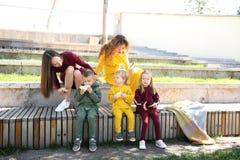 ευτυχείς μητέρες με τα παιδιά στο πάρκο στα ενδύματα οικογένεια-ύφους στοκ φωτογραφία