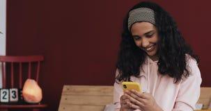 Ευτυχείς να κουβεντιάσει και αποστολή κειμενικών μηνυμάτων κοριτσιών αφροαμερικάνων στη συνεδρίαση smartphone στο κρεβάτι στο σπί απόθεμα βίντεο