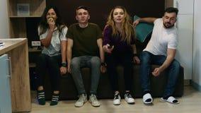 Ευτυχείς τέσσερις φίλοι άρχισαν να προσέχουν τη TV από κοινού Έννοια φιλίας και ψυχαγωγίας απόθεμα βίντεο