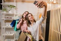Ευτυχείς φίλες που κάνουν selfie με τις τσάντες αγορών στοκ εικόνες
