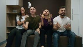 Ευτυχείς φίλοι ή οπαδοί ποδοσφαίρου που προσέχουν τον αθλητικό αγώνα στη TV και που γιορτάζουν τη νίκη στο σπίτι Φιλία, αθλητισμό απόθεμα βίντεο