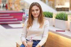 Ευχάριστο να φανεί νέο θηλυκό που ντύνεται στον άλτη και τα τζιν, ποτά milkshake, κάθεται στη λεωφόρο αγορών ενάντια στην πρασινά στοκ φωτογραφία με δικαίωμα ελεύθερης χρήσης