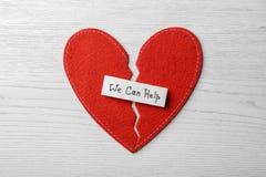 Επίπεδος βάλτε τη σύνθεση με τα μισά αισθητών της κόκκινο καρδιάς και της σημείωσης που ΜΠΟΡΟΥΜΕ ΝΑ ΒΟΗΘΗΣΟΥΜΕ στοκ εικόνα με δικαίωμα ελεύθερης χρήσης