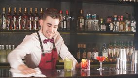 Επαγγελματικό νέο bartender σε ομοιόμορφο σκουπίζει το φραγμό πριν από την έναρξη της μετατόπισης εργασίας απόθεμα βίντεο