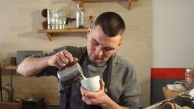 Επαγγελματικό barista που χύνει το βρασμένο στον ατμό γάλα στο φλυτζάνι καφέ που κάνει latte την τέχνη απόθεμα βίντεο