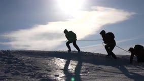 Επιθυμία ομαδικής εργασίας να κερδίσει Οι ορειβάτες σε ένα σχοινί βοηθούν έναν φίλο να αναρριχηθεί στην κορυφή του λόφου Σκιαγραφ στοκ φωτογραφίες