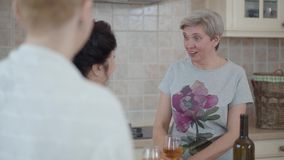 Επικοινωνία τριών ώριμη γυναικών που κουβεντιάζει στην κουζίνα στο σπίτι με το κρασί στον πίνακα Μια κυρία που ενώ φιλμ μικρού μήκους