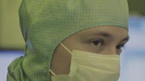 Επιστήμονας μηχανικών στα αποστειρωμένα κοστούμια, μάσκα είναι σε μια καθαρή περιοχή, εξετάζοντας ένα τεχνολογικά προηγμένο εργασ φιλμ μικρού μήκους