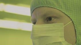 Επιστήμονας μηχανικών στα αποστειρωμένα κοστούμια, μάσκα είναι σε μια καθαρή ζώνη εξετάζοντας ένα διαδικασίας προηγμένης τεχνολογ φιλμ μικρού μήκους