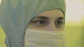 Επιστήμονας μηχανικών στα αποστειρωμένα κοστούμια, μάσκα είναι σε μια καθαρή ζώνη εξετάζοντας ένα διαδικασίας προηγμένης τεχνολογ απόθεμα βίντεο