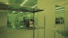 Επιστήμονας μηχανικών στα αποστειρωμένα κοστούμια, μάσκα είναι στην καθαρή ζώνη, παίρνει τα προϊόντα μικροτσίπ Καθαρή υψηλή τεχνο απόθεμα βίντεο