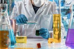 Επιστήμονας που αναμιγνύει τα ρευστά με έναν σωλήνα δοκιμής και μια φιάλη για το εργαστηριακό testin στοκ εικόνες