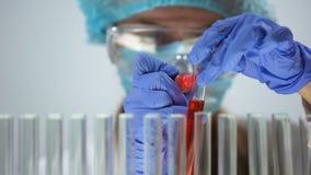 Επιστήμονας που χαρακτηρίζει το σωλήνα με το κόκκινο υγρό, που διευθύνει την ανάλυση δειγμάτων, cosmetology φιλμ μικρού μήκους