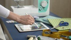 Επιτραπέζιο seamstress ενδύματα σχεδιαστών, πλάγια όψη, μπλε υπόβαθρο απόθεμα βίντεο