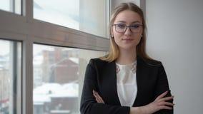 Επιτυχής επιχειρηματίας γυναικών πορτρέτου στο επιχειρησιακό κοστούμι και γυαλιά κοντά στο παράθυρο απόθεμα βίντεο