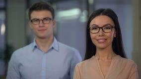 Επιτυχείς συνάδελφοι που εξετάζουν με βεβαιότητα τη κάμερα, ομάδα νεοσύστατης εταιρείας απόθεμα βίντεο