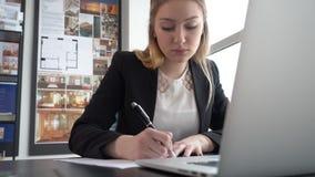 Επιχειρηματίας γυναικών που γράφει με το επιχειρησιακό έγγραφο μανδρών σχετικά με τον πίνακα στο σύγχρονο γραφείο φιλμ μικρού μήκους