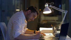 Επιχειρηματίας με τα έγγραφα και το γραφείο lap-top τη νύχτα φιλμ μικρού μήκους