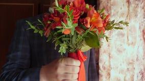 Επιχειρηματίας με τα όμορφα λουλούδια Όμορφη ανθοδέσμη των κόκκινων τριαντάφυλλων στα χέρια των ατόμων στο σακάκι σε έναν κόκκινο απόθεμα βίντεο