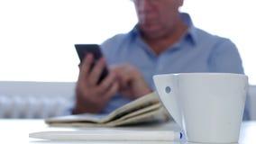 Επιχειρηματίας με τον καφέ και εφημερίδα Texting που χρησιμοποιούν το δίκτυο ραδιοφώνων κινητών τηλεφώνων φιλμ μικρού μήκους