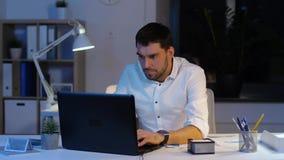 Επιχειρηματίας με το lap-top που λειτουργεί τη νύχτα το γραφείο φιλμ μικρού μήκους