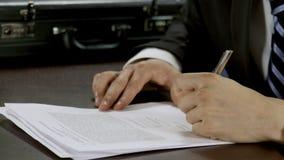 Επιχειρηματίας στην επίσημη ένδυση που υπογράφει την κινηματογράφηση σε πρώτο πλάνο συμβάσεων στο γραφείο φιλμ μικρού μήκους