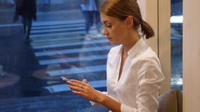 Επιχειρηματίας στο άσπρο πουκάμισο με το smartphone ενάντια στο παράθυρο φιλμ μικρού μήκους