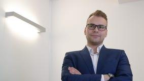 Επιχειρηματίας σχετικά με eyeglasses και στάση με τα διασχισμένα χέρια στο στήθος φιλμ μικρού μήκους
