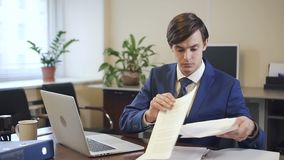 Επιχειρηματίας που εργάζεται στο lap-top και με το έγγραφο εγγράφου στο σύγχρονο γραφείο απόθεμα βίντεο