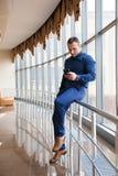 Επιχειρηματίας που κοιτάζει μέσω του τηλεφώνου από το παράθυρο στοκ φωτογραφία με δικαίωμα ελεύθερης χρήσης