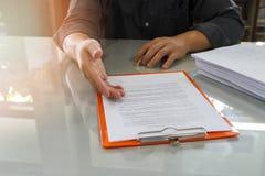 Επιχειρηματίας που προσφέρει το έγγραφο συμβάσεων στο συνέταιρο του για τη σύμβαση σημαδιών στοκ φωτογραφίες