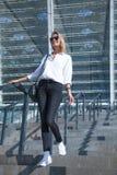 Επιχειρησιακή γυναίκα στα γυαλιά ηλίου που περπατά στην οδό στοκ εικόνες