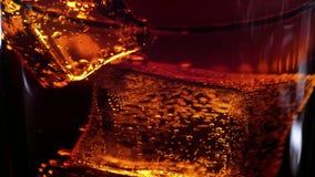 Επιπλέων κύβος πάγου σε ένα ποτήρι της κόλας - ποτό σόδας σε σε αργή κίνηση απόθεμα βίντεο