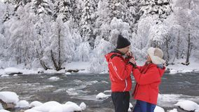 Ζεύγος ερωτευμένο κοντινός ένας ποταμός βουνών στο χειμερινό δάσος που μιλά και που φλερτάρει φιλμ μικρού μήκους