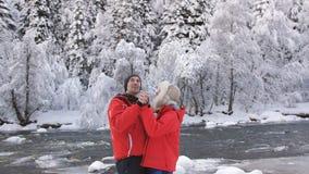 Ζεύγος ερωτευμένο στις όχθεις ενός ποταμού βουνών το χειμώνα που απολαμβάνει το χειμερινά τοπίο και το αγκάλιασμα απόθεμα βίντεο