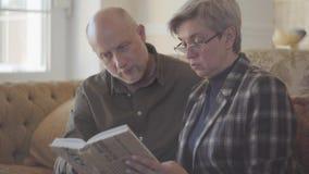 Ζεύγος, ηληκιωμένος και γυναίκα, που κάθονται στον καναπέ με ένα βιβλίο και που μιλούν και που χαμογελούν ο ένας στον άλλο Οικογε φιλμ μικρού μήκους