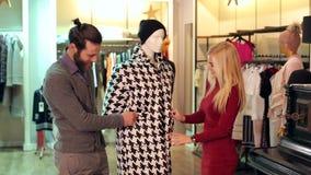 Ζεύγος που ψωνίζει μαζί στο κατάστημα ιματισμού, εξετάζουν το παλτό απόθεμα βίντεο