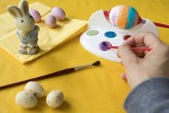 Ζωγραφική των αυγών Πάσχας με την κόκκινη βούρτσα στοκ εικόνες