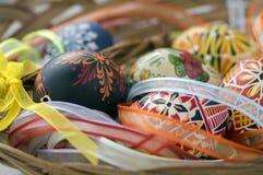 Ζωηρόχρωμα χρωματισμένα αυγά Πάσχας στο καφετί ψάθινο καλάθι που καλύπτεται με τις ζωηρόχρωμες κορδέλλες, παραδοσιακή ζωή Πάσχας  στοκ φωτογραφία με δικαίωμα ελεύθερης χρήσης