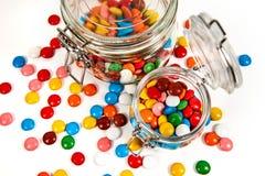 Ζωηρόχρωμες καραμέλες στο βάζο γυαλιού διεσπαρμένο που απομονώνεται στο λευκό στοκ φωτογραφία με δικαίωμα ελεύθερης χρήσης