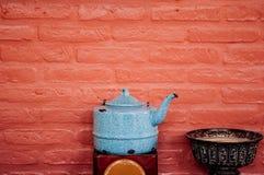 Ζωηρόχρωμο εκλεκτής ποιότητας δοχείο κατσαρολών και μαύρος παλαιός δίσκος βάθρων με το υπόβαθρο τουβλότοιχος στοκ εικόνα