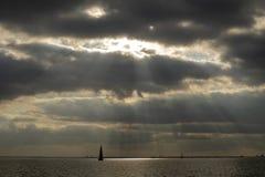 Ηλιαχτίδες που σπάζουν μέσω της κάλυψης σύννεφων, sailboat που πλέει με μια λίμνη κοντά στο Άμστερνταμ στοκ φωτογραφία