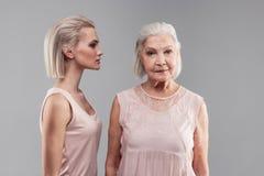 Ηλικιωμένη γκρίζος-μαλλιαρή γυναίκα με το βαρίδι hairstyle που κοιτάζει άμεσα στη κάμερα στοκ φωτογραφία