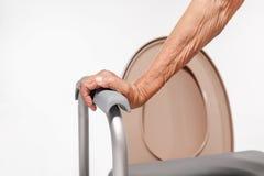 Ηλικιωμένη γυναίκα που χρησιμοποιεί την κινητή καρέκλα καθισμάτων τουαλετών στοκ φωτογραφία