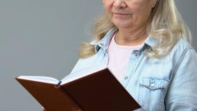 Ηλικιωμένο συνταξιούχο θηλυκό βιβλίο ανάγνωσης, σκέψη την ενδιαφέρουσα ιστορία ιδιωτικών αστυνομικών απόθεμα βίντεο