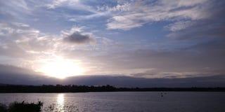 Ηλιοβασίλεμα στα σύννεφα κατά την άποψη λιμνών στοκ φωτογραφία